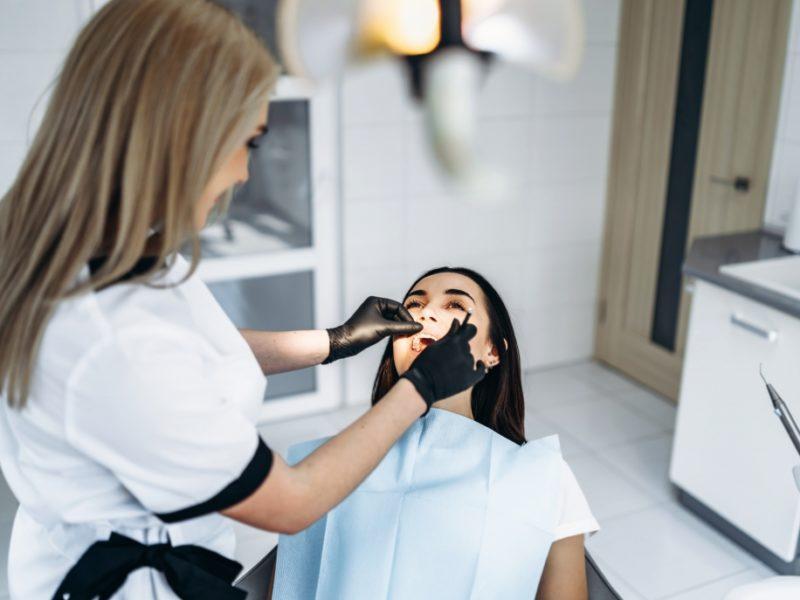 Woman getting teeth examined by dentist